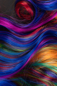 Abstract background of multicolored vibrant soft hair locks in mess