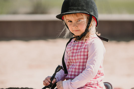 Small girl in dress and jockey hay sitting on horse while learning to ride on racetrack