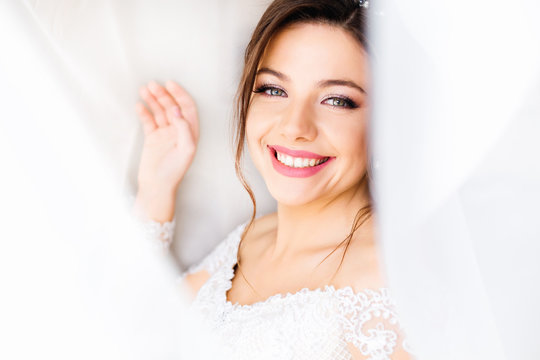Beautiful bride in white dress look at camera and smile under cu
