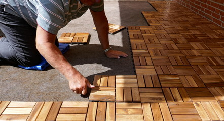 A craftsman is laying wooden tiles on a terrace. It connects square wood panels with Lock Clic