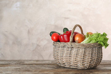 Wicker basket with ripe vegetables on wooden table. Space for text