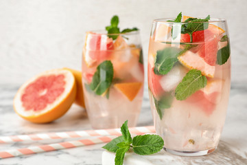 Glasses of refreshing drink with grapefruit and mint on marble table, space for text