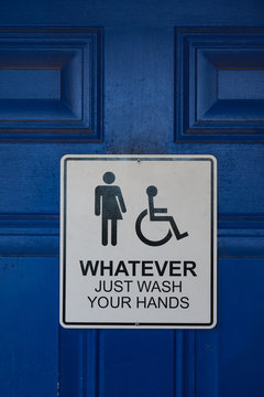 "Sign on a blue restroom door says ""Whatever Just Wash Your Hands"" and includes male, female, and handicapped symbols"