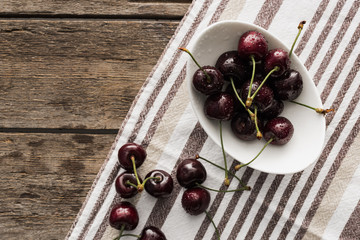 top view of fresh, whole and ripe cherries covered with water drops on bowl