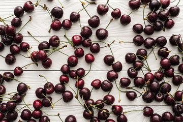 top view of fresh, sweet and ripe cherries covered with droplets on wooden background