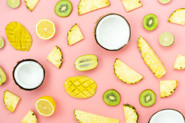 Table top view fruit tropical with spring summer holiday & vacation  background concept.Arrangement sliced various pineapple kiwi mango lemon and lime coconut on  pink paper.flat lay & pastel tone.