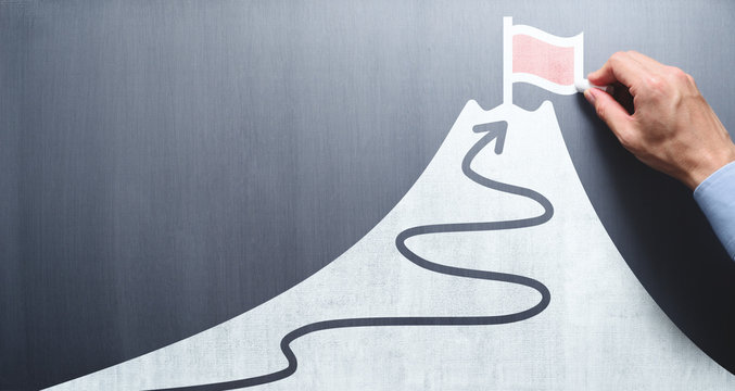 Business goal and success concept. Businessman drawing flag and mountain on chalkboard.