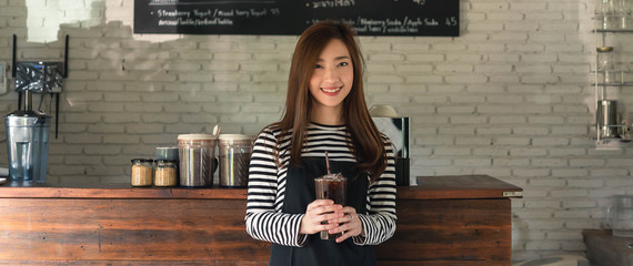 Woman coffee shop owner serving ice americano, young entrepreneur, dimenstion image for banner