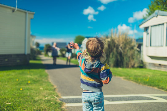 A little toddler is standing in a trailer park waving to his family