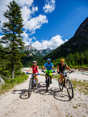 Wall Mural - Cycling family riding on bikes in Dolomites mountains landscape. Couple cycling MTB enduro trail track. Outdoor sport activity.