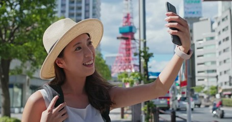 Wall Mural - Woman travel in Japan, take selfie on mobile phone in Tokyo city
