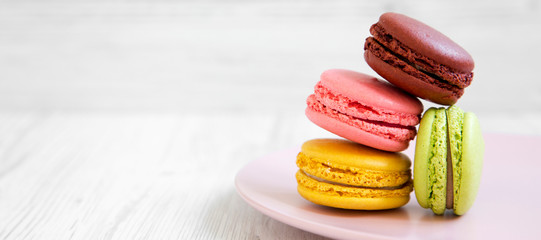 Foto op Textielframe Macarons Sweet and colorful macarons on a pink plate over white wooden background, side view. Copy space.