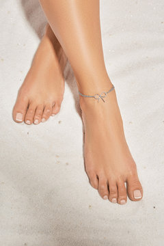 Cropped front shot of girl's legs with french pedicure, wearing silver ankle bracelet, decorated with silver insertion in view of tied bow. The lady is crossing her legs, lying on the sandy platform.