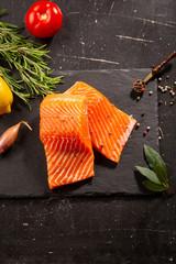 Two slice of salmon fish on slate