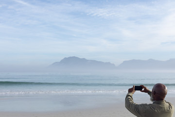 Man taking a picture at the beach