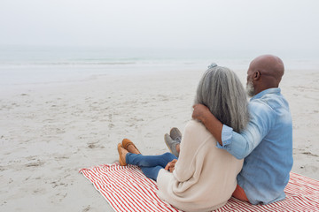 Couple sitting on red and white striped picnic blanket at the beach