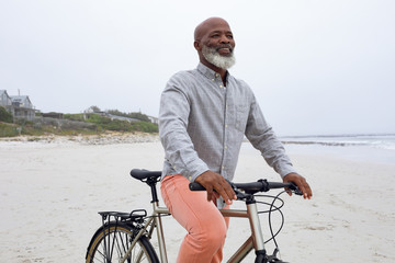 Man riding a bicycle at the beach.