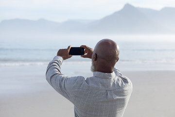 Man taking a picture of the beach.