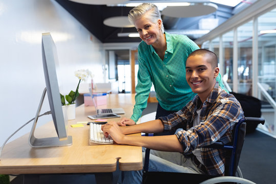 Male and female executives working together on computer at desk in office