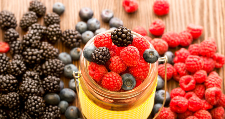 different berries in a basket on a wooden table
