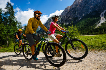 Wall Mural - Tourist cycling in Cortina d'Ampezzo, stunning rocky mountains on the background. Family riding MTB enduro flow trail. South Tyrol province of Italy, Dolomites.