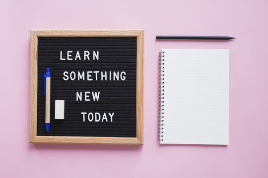 Stationeries with learn something new today text on slate over pink backdrop