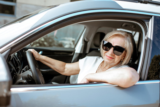 Portrait of a senior woman driver sitting in the modern car, looking out the window. Concept of an active people during retirement age