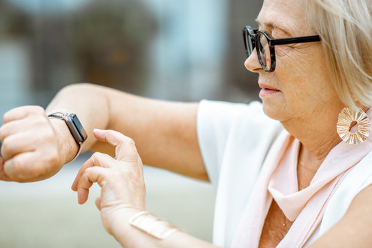 Senior woman using smart watch outdoors. Concept of using modern technologies by elderly people