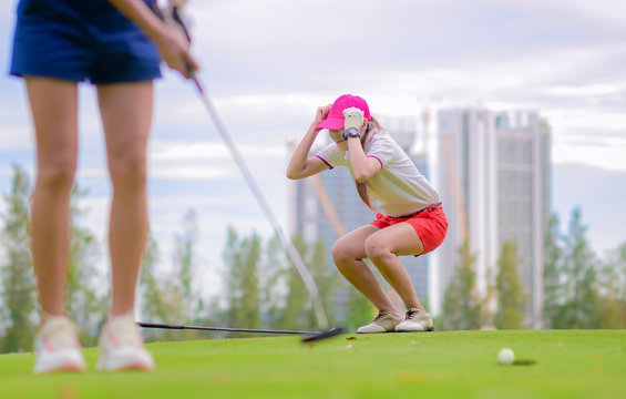 young woman golf player acting upset disaster or disturb or disappointed in golf ball putting successfully into hole by another opponent competitor