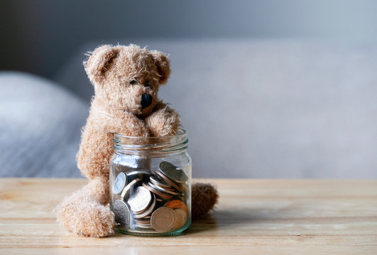 Teddy bear putting hand into the jar of British coins on wooden table , Brown bear sitting next to clear glass jar with pound coins, Money saving concept