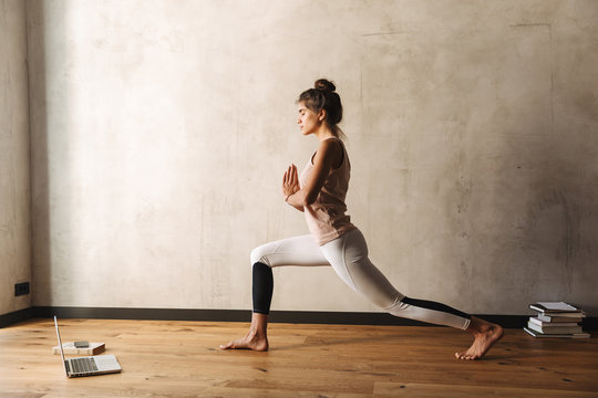 Photo of concentrated woman doing yoga exercises with closed eyes and palms together at home