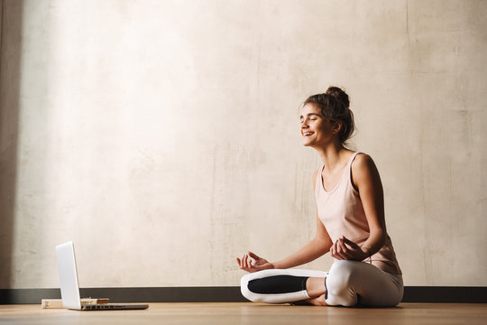 Photo of joyful fitness woman meditating with zen fingers and laughing while sitting on floor with laptop at home