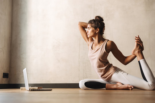 Photo of pretty concentrated woman doing yoga exercises using laptop while sitting on floor at home