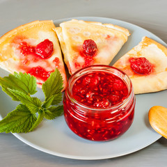 Glass jar with raspberry jam with homemade pancakes, fresh berries and mint on a gray background.Copy space
