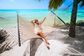 Printed kitchen splashbacks Zanzibar Woman is relaxing in a hammock on the beach among the palm near the sea.