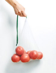 Hand holding a reusable eco bag with tomatoes.
