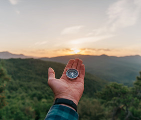Compass on male palm hand in summer mountains at sunrise, pov.