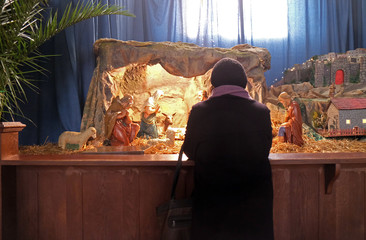 A woman prays in front of the Christmas creches in the Basilica of the Sacred Heart in Zagreb