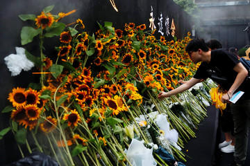 Pro-democracy activists lay sunflowers at a memorial site for anti-extradition bill protester Marco Leung, who died after falling from a scaffolding at the Pacific Place complex while protesting, in Hong Kong