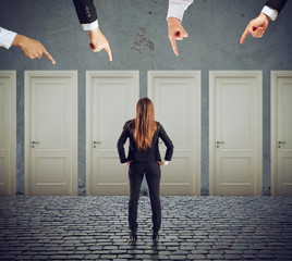 Businesswoman looking to select the right door. Concept of confusion and competition