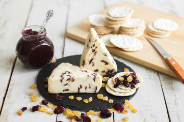 Cranberry cheese served on black slate board with crackers, cranberry sauce and raisin. Sweet cheese