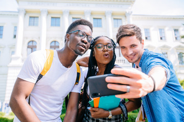 Picture of multiethnic group of three young happy students standing outdoors make selfie by phone. Looking aside.