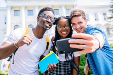 The team of young students sitting outdoors make selfie by phone. with university building on background and looking at smart phone. Group of students