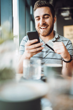 Portrait of smiling man using smart phone and credit card in local cafe. shopping online with credit card