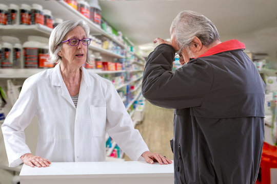men having headache talking to the pharmacist while shopping for painkillers at the local drugstore