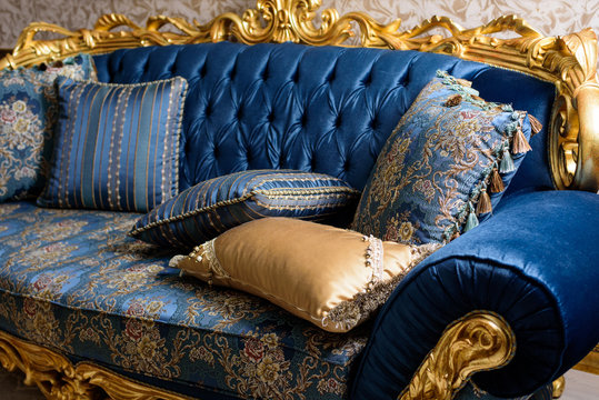 Luxury blue sofa with pillows. Baroque style.