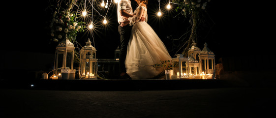 Beautiful couple is hugging near white flowers arch at the wedding ceremony. Outdoors decoration. Romantic rustic style. Lamps lights in the evening. Bride and groom together.