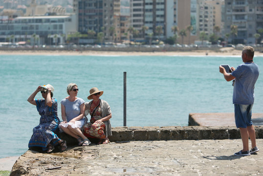 A tourist uses an iPad to take a picture of fellow tourists at the sea castle in the port city of Sidon