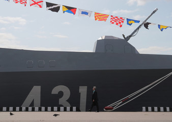 A man walks past the Russian frigate Admiral Kasatonov during the International Maritime Defence Show 2019 in St. Petersburg