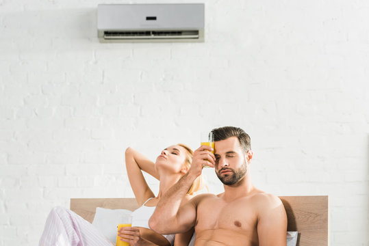couple with orange juice suffering from heat under air conditioner in bed at home